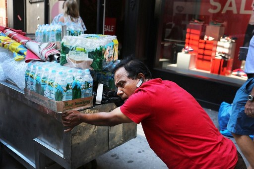 A man pushes a cart of bottled water down Broadway during warm weather on July 6, 2012 in New York City. ©AFP