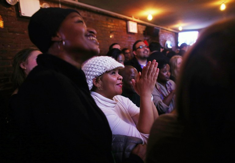 Akilah Rosado (C) and others watch U.S. President Barack Obama's State of the Union speech at a watch party sponsored by the Democratic Leadership for the 21st Century (DL21C) and Manhattan Young Democrats (MYD) at Smithfield NYC. ©AFP