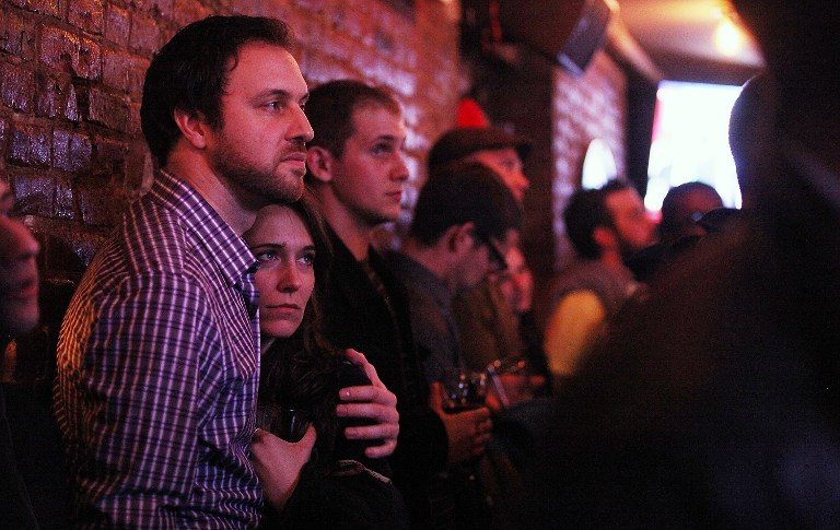 People watch U.S. President Barack Obama's State of the Union speech at a watch party sponsored by the Democratic Leadership for the 21st Century (DL21C) and Manhattan Young Democrats (MYD) at Smithfield NYC. ©AFP