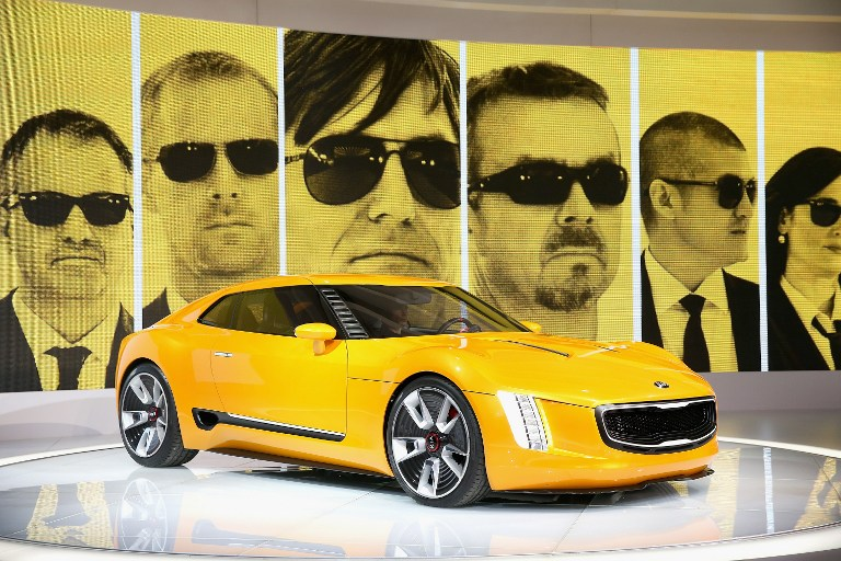 With members of the design team projected behind it, Kia introduces the GT4 Stinger concept sports car at the North American International Auto Show (NAIAS) on January 13, 2014 in Detroit, Michigan.