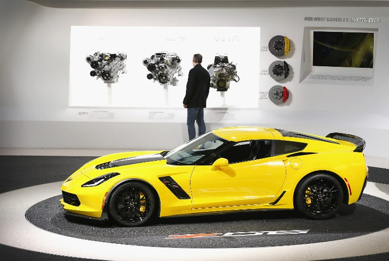 A visitor looks over engine options on display next to a 2015 Chevrolet ZO6 Corvette at the North American International Auto Show (NAIAS) on January 14, 2014 in Detroit, Michigan.