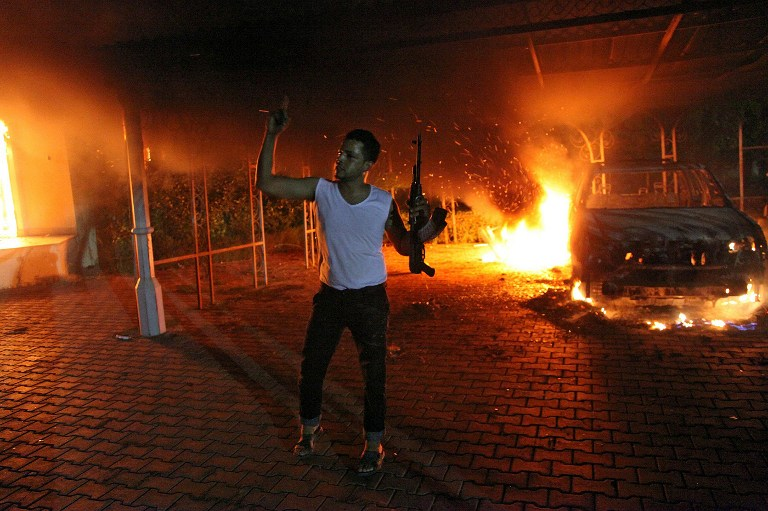 An armed man waves his rifle as buildings and cars are engulfed in flames after being set on fire inside the US consulate compound in Benghazi. ©AFP