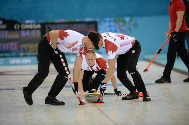 Canada's Brad Jacobs (C) watches his stone during the 2014 Sochi winter olympics men's curling. ©AFP