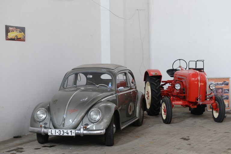 A Volkswagen Beetle (L) and a Porsche tractor are displayed in a hall of car collector Milan Bumba in Vratislavice village