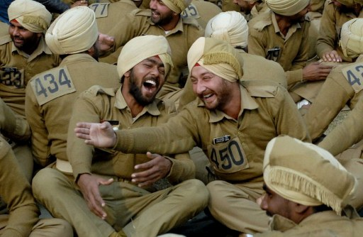 Indian police constables share a light moment as they participate in a yoga laughing therapy session. ©AFP