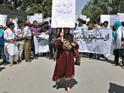 An Afghan woman, holding a placard which reads