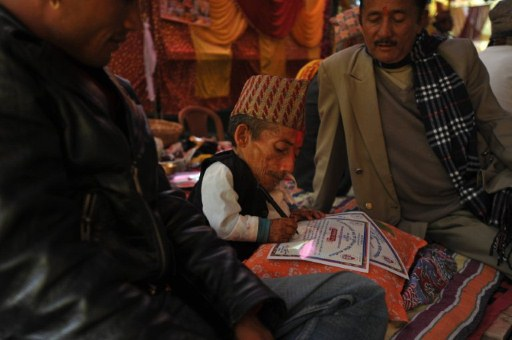 Chandra Bahadur Dangi (C), a 72-year-old Nepali who claims to be the world's shortest man at 56 centimetres (22 inches) in height signs a certificate. ©AFP