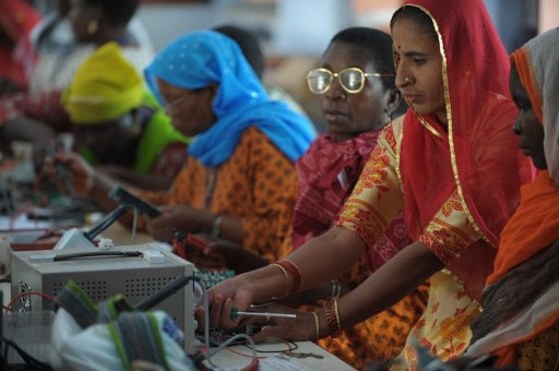 Magan Kanwar, 45, (2nd R) teaches to integrate circuit boards for solar lights at the Barefoot College. ©AFP