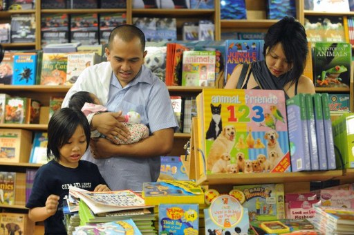 A Filipino family looks at books on board the Logos Hope. ©AFP