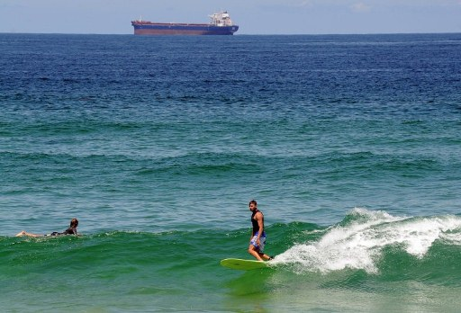 Surfers ride the waves at Redhead Beach. ©AFP