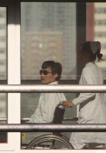 Chinese activist activist Chen Guangcheng (L) is seen in a wheelchair pushed by a nurse at the Chaoyang hospital in Beijing.©AFP PHOTO/Jordan Pouille