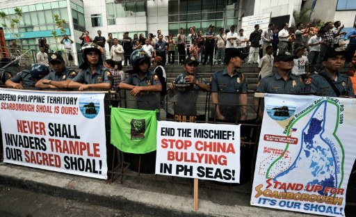 Philippine policemen stand guard next to anti-China placards displayed during a rally in front of the Chinese consulate. ©AFP