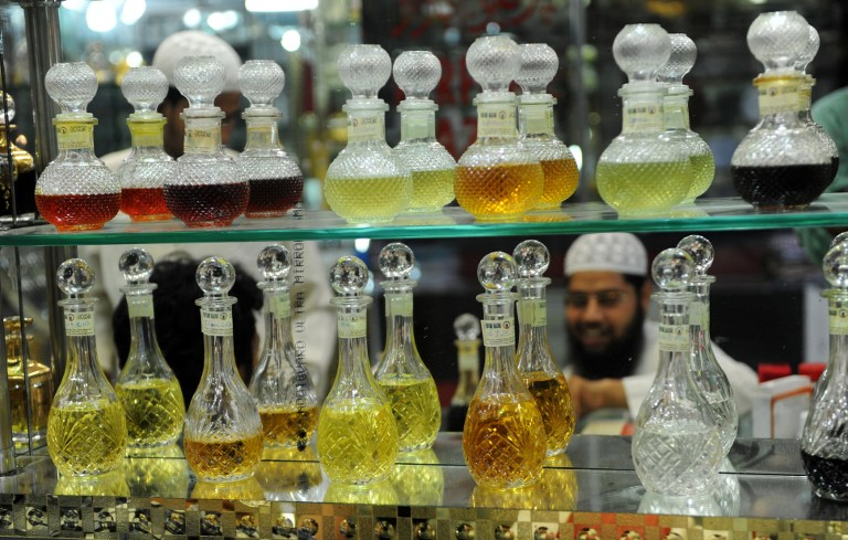 An Indian Muslim tests Attar, perfume, before purchasing it at a shop. ©AFP