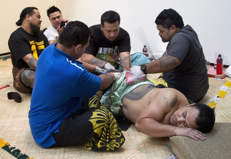 Ricky Masoe (bottom R) lying down as assistants (L) hold his skin tight while master tattooist Su'a Paul Sulu'ape (R) uses a traditional method to tattoo him. ©AFP