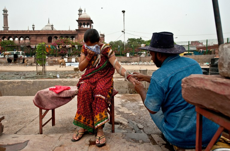 An Indian woman covers her face in pain as she is cut on her hand by Mohammed Iqbal. ©AFP