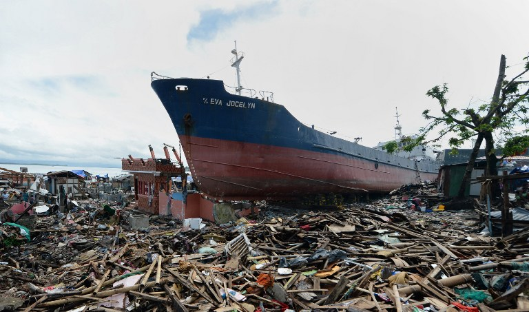 A cargo ship swept ashore at the height of Super Typhoon Haiyan still rest amongst debris and destroyed houses weeks after the storm in the coastal city of Tacloban, Leyte province, on December 24, 2013, on the eve of Christmas.