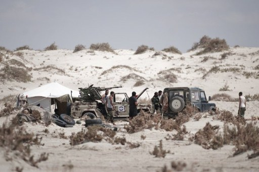 Libyan rebels fighters walk past their armored pick-up trucks on the oustskirts of Brega. ©AFP