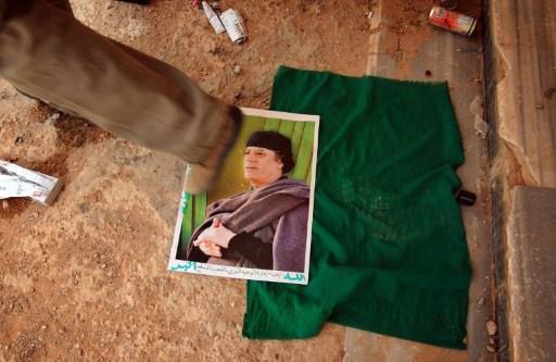 A Libyan rebel walks on top of a picture of Libyan leader Moamer Kadhafi. ©AFP
