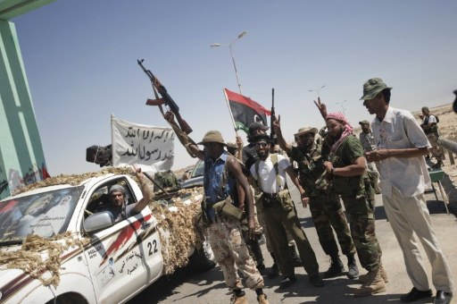 Libyan rebels celebrate as they man a check point at the entrance of the residential area of Brega, on August 15, 2011. ©AFP