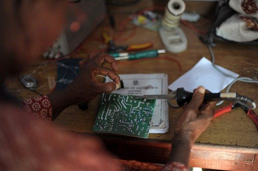 A woman working on some soldering during a workshop to learn how to integrate circuit boards. ©AFP