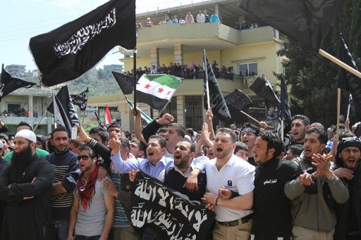 Lebanese and Syrian supporters of Sunni Muslim Salafist leader Ahmed al-Asir chant slogans as they hold religious banners and a pre-Baath Syrian flag during an anti-Syrian regime demonstration. ©AFP