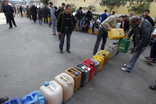 Palestinians wait in a queue to fill containers with fuel at a petrol station in Gaza City. ©AFP