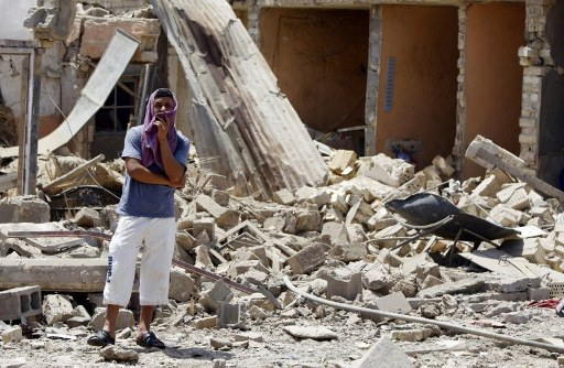 An Iraqi man stands amdist the rubble of destroyed houses following a series of bomb attacks. ©AFP