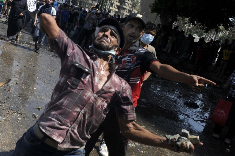 Egyptian protesters throw stones to the riot police during clashes near the US embassy in Cairo. ©AFP