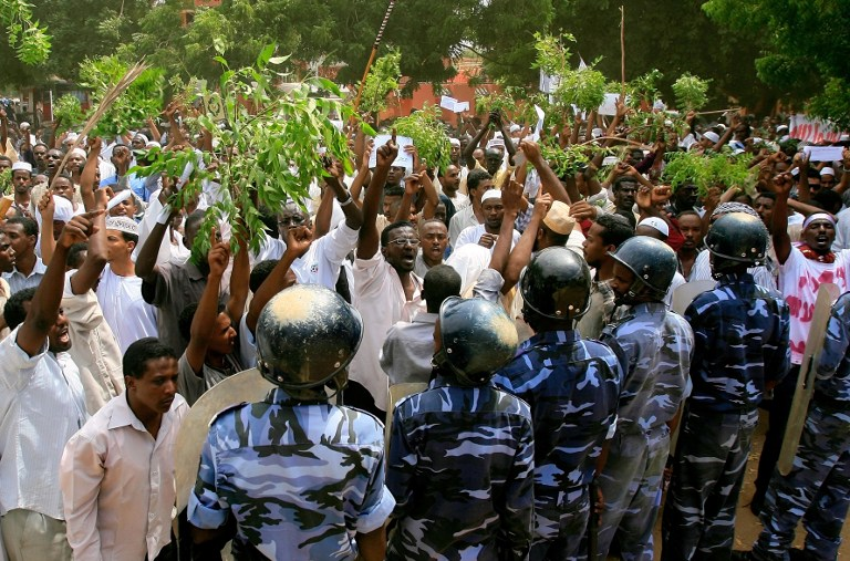 Sudanese policemen stand guard opposite demonstrators during a protest against an amateur film mocking Islam. ©AFP