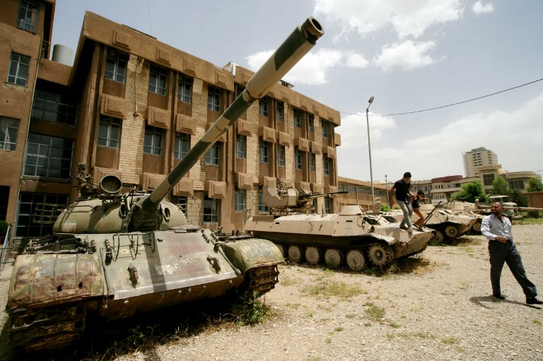 Iraqi Kurds look at tanks as they visit a former torture centre that was turned into a museum. ©AFP