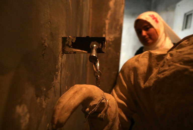 An Iraqi Kurd visitor visits a cell at a former torture centre that was turned into a museum. ©AFP