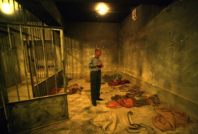 An Iraqi Kurd visitor stands in a cell at a former torture centre. ©AFP
