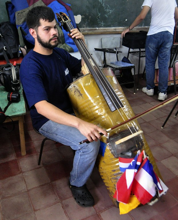 A musician from a Paraguayan juvenile symphonic orchestra shows his cello made out of recycled trash during a rehearsal in Asuncion. ©AFP