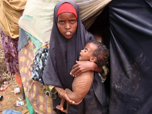 An internally displaced young woman carries her child to a medical centre at a camp for the displaced persons. ©AFP PHOTO/Mustafa ABDI