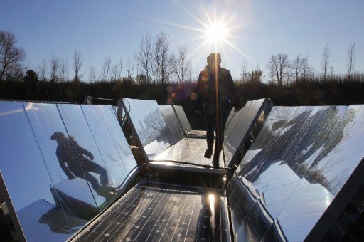 Engineers check a floating photovoltaic panel system. ©AFP