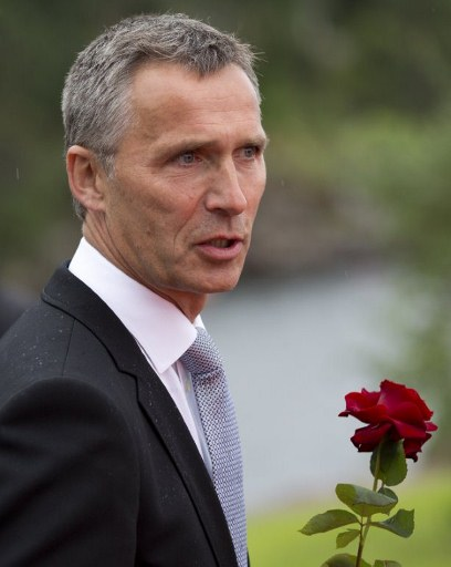 Norway's Prime Minister Jens Stoltenberg holds a flower on his way to the wreath laying ceremony. ©AFP