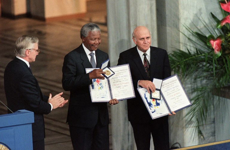 A file photo taken on December 10, 1993 shows Nelson Mandela (C), the President of the South African African National Congress and South African President Frederik de Klerk (R) displaying their Nobel Prizes after being awarded jointly for their work to end apartheid peacefully during a ceremony in Oslo. ©AFP