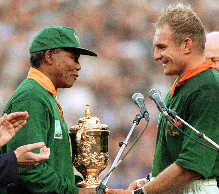 A file photo taken on June 24, 1995 shows South African President Nelson Mandela congratulating South Africa's rugby team captain Francois Pienaar before handing him the Webb Ellis Cup after the 1995 Rugby World Cup final match between South Africa and New Zealand at Ellis Park Stadium in Johannesburg.