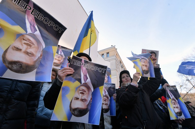Protesters hold rotated pictures of Ukrainian President Viktor Yanukovych and signed