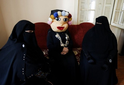 An Egyptian woman wearing a mask and two niqab-clad women attend an editorial meeting on a children's TV show at Egypt's new Maria TV studios. ©AFP