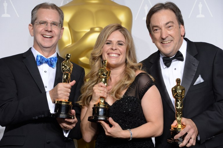 Directors Chris Buck (L) and Jennifer Lee (C) stand with producer Peter Del Vecho (R) after winning the Best Animated Feature Film award for 'Frozen'.©AFP