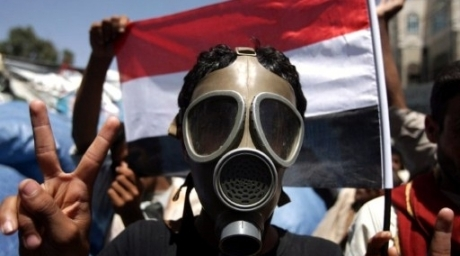 A Yemeni opposition demonstrator wearing a gas mask flashes the victory sign during an anti-regime protest in Sanaa. ©AFP