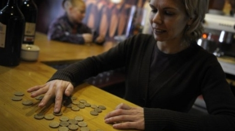 The owner of a coffe-bar counts pesetas coins in Salvaterra de Mino, northwestern Spain. ©AFP