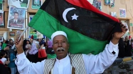 A Libyan man holds his new flag during celebrations in the eastern coastal city of Benghazi on October 20, 2011. ©AFP