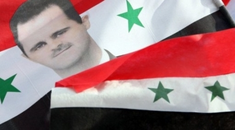 A portrait of Syrian President Bashar al-Assad is seen on a national flag carried by pro-regime supporters during a rally in Damascus. ©AFP