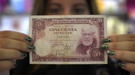 A sales clerk shows a 50 pesetas note collected at her store in Salvaterra de Mino, northwestern Spain. ©AFP