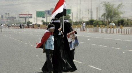 Supporters of Yemeni President Ali Abdullah Saleh (portrait) walk towards a main Sanaa square. ©AFP