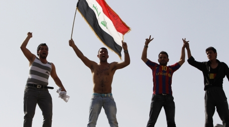 A resident waving an Iraqi flag demonstrate with fellow protesters in Central Baghdad. ©Reuters
