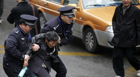 Police arrest a man in front of the Peace Cinema in downtown Shanghai, after calls for a