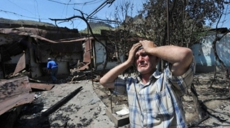 An ethnic Uzbek man stands beside the wreckage of his home, which was burned out during days of deadly ethnic violence in Osh. ©AFP